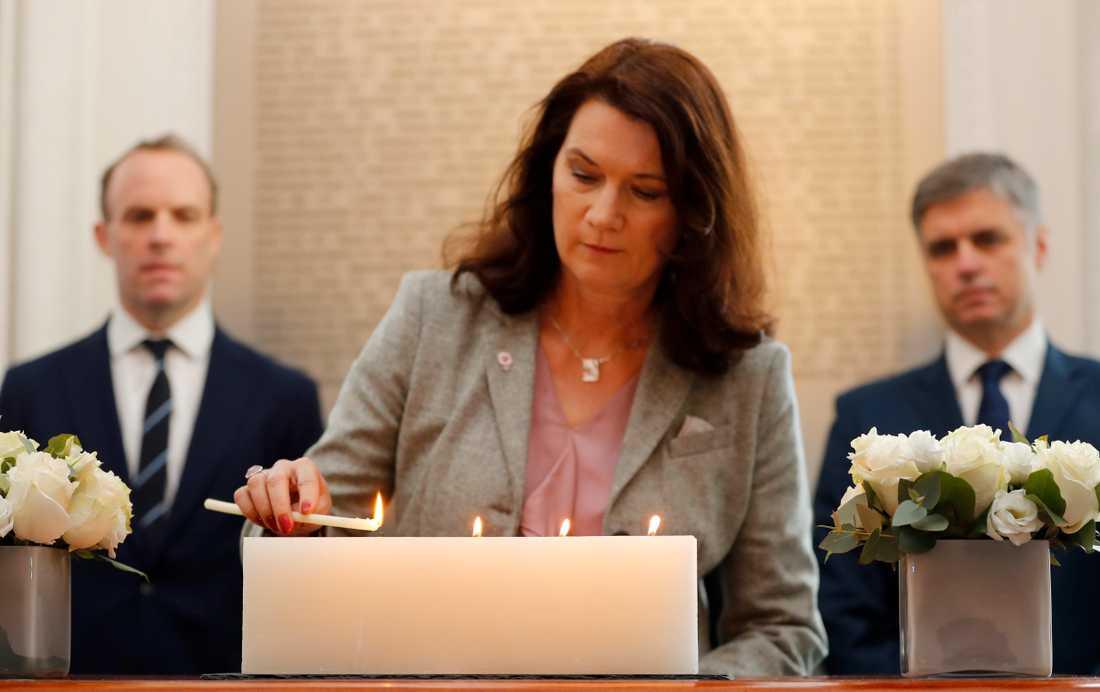 Utrikesminister Ann Linde (S) tänder ett ljus framför en minnesskylt med namnen på de som dödades i nedskjutningen av det ukrainska passagerarflygplanet i Iran.