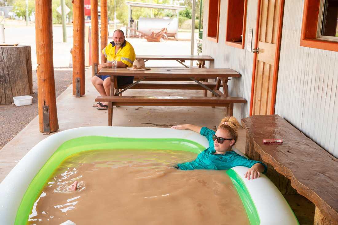 Jasmin Kew svalkar sig i en uppblåsbar pool med missfärgat kranvatten i den 47 gradiga hettan.