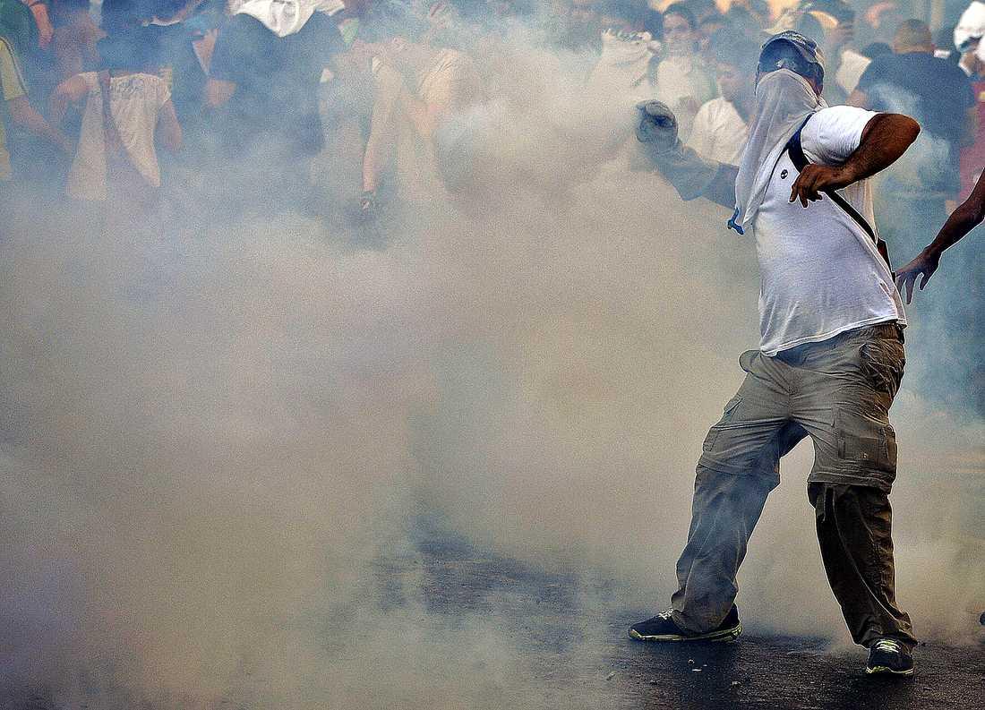 Oppositionella studenter i huvudstaden Caracas kastar sten mot polisen.