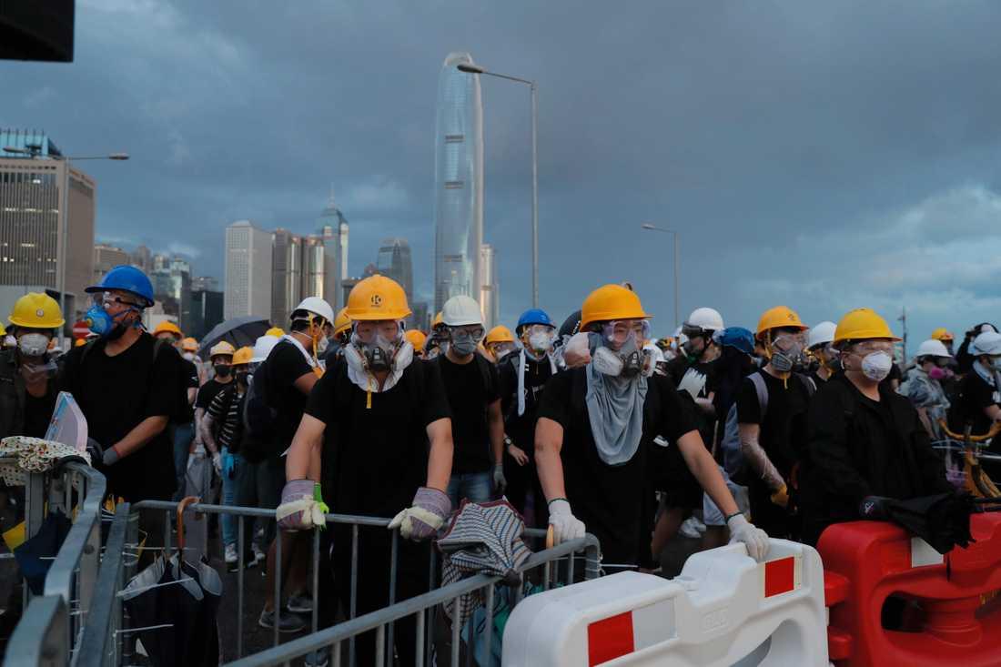 Demonstranterna, klädda i gasmasker och hjälmar, blockerar en väg under protesterna i Hongkong.