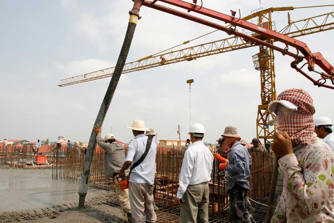 Byggnadsarbetare ser på medan cement fyller upp ett nytt lägenhetskomplex i Phnom Penh 2008. De senaste årtiondena har land- och huspriserna i huvudstaden skjutit i höjden.