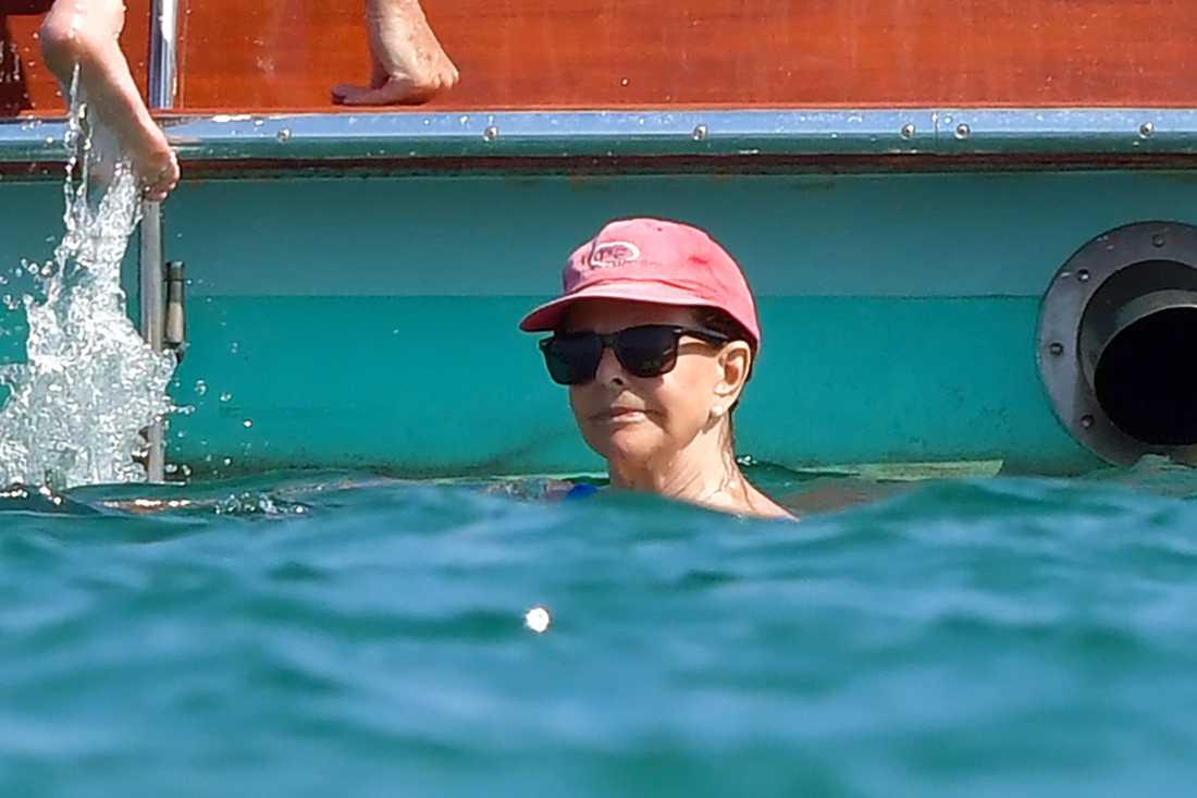 Drottningen, i keps och solglasögon, badar i havet.