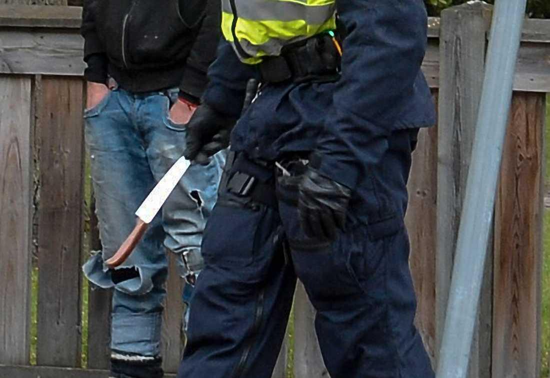 En polis bär bort en kniv som har beslagtagits i samband med en demonstration. Arkivbild.