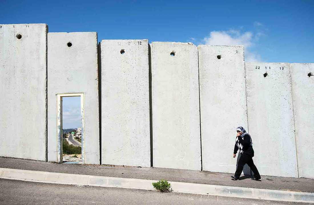 Muren vid byn Waladja i Palestina ligger på gränsen till Jerusalem. Shirine Al-Araj, är på väg att gå igenom en öppning i muren.
