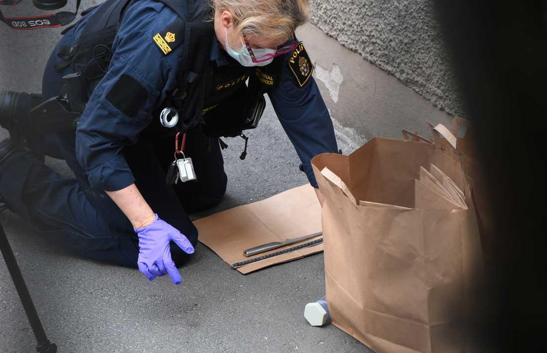 Polisens tekniker undersöker en kniv som hittats på platsen för överfallet