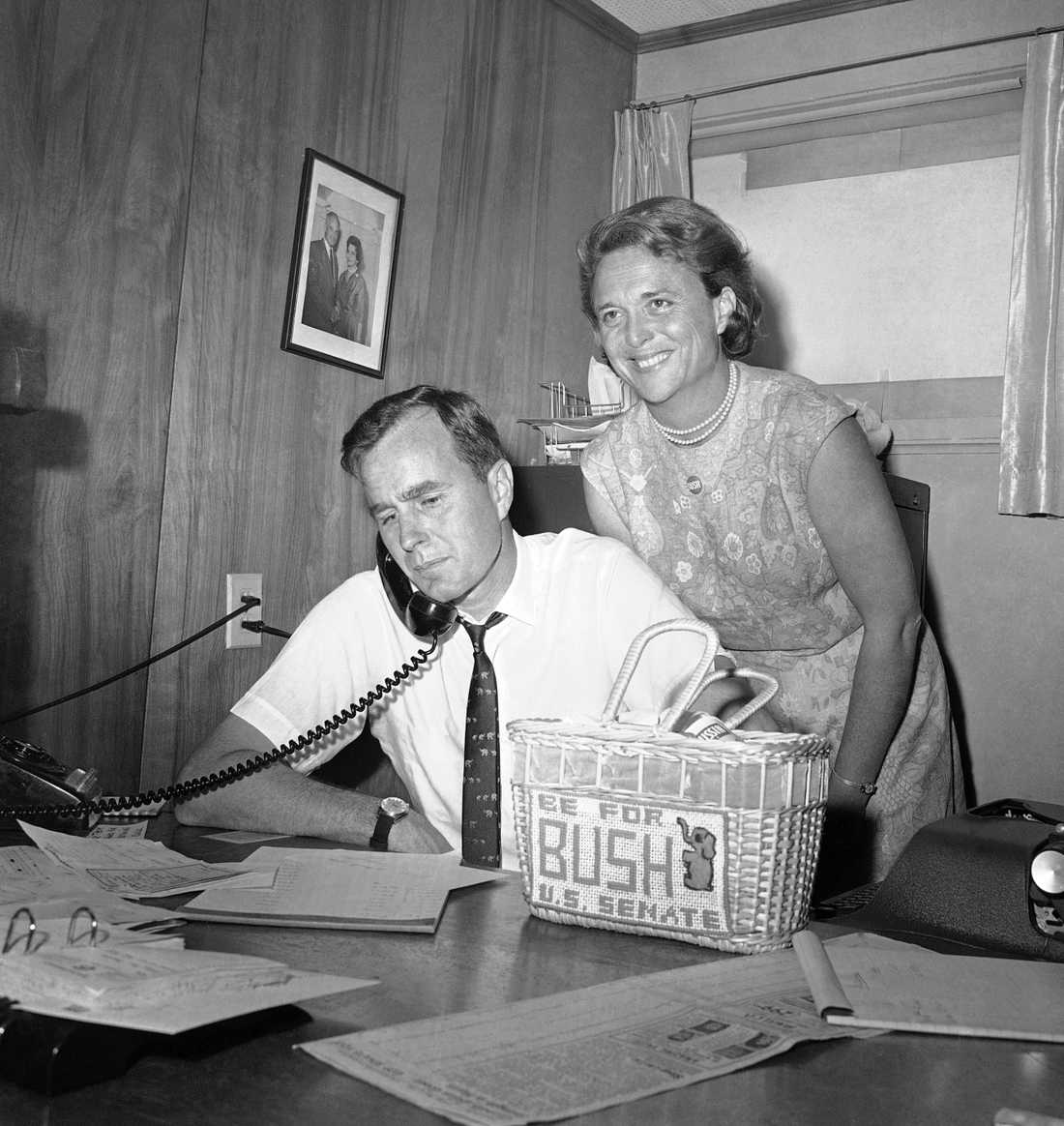 n this June 6, 1964, file photo George H.W. Bush, candidate for the Republican nomination for the U.S. Senate, gets returns by phone at his headquarters in Houston, as his wife Barbara, smiles at the news.