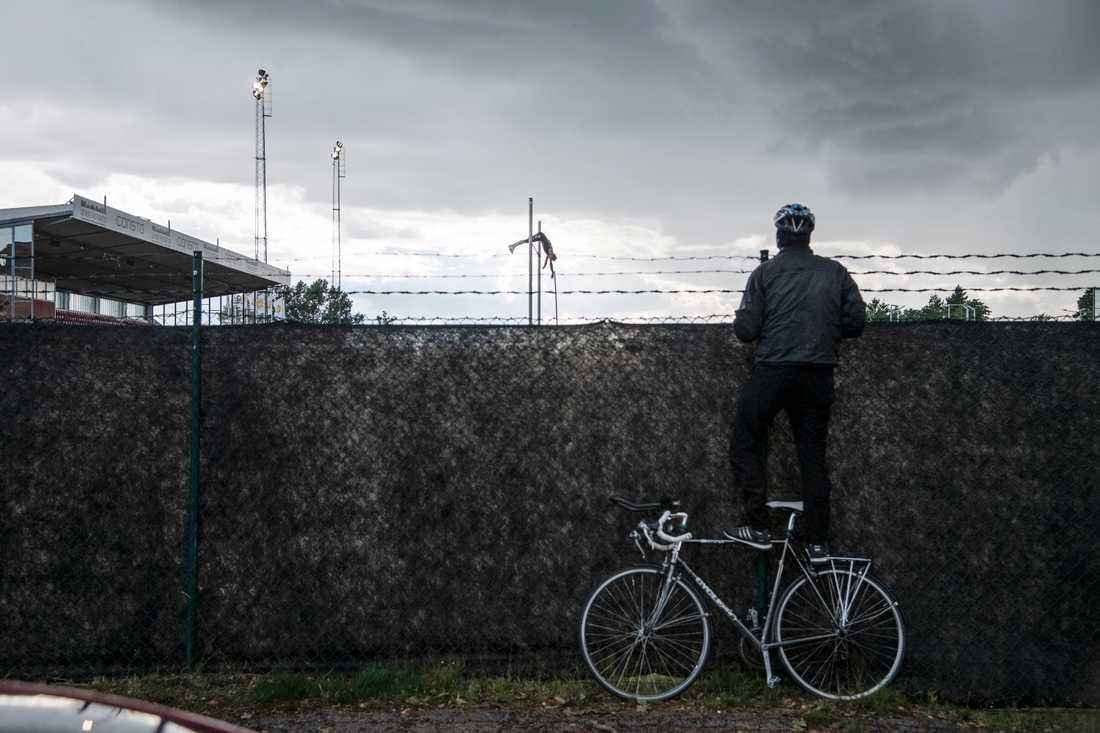 En man står på sin cykel för att se över staketet när Armand Duplantis vinner herrarnas stavhopp på 5,72 meter i friidrottstävlingen Karlstad GP den 8 juli 2020 på Tingvalla IP. På grund av coronapandemin tillåts ingen publik på arenan.