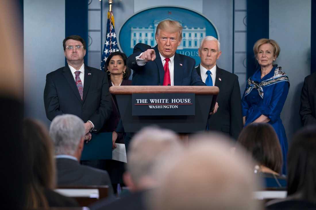 USA:s president Donald Trump utnyttjar en krigstidslag för att utöka produktion av medicinsk utrustning. Här på en presskonferens med bland andra vicepresident Mike Pence och medarbetare på onsdagen.