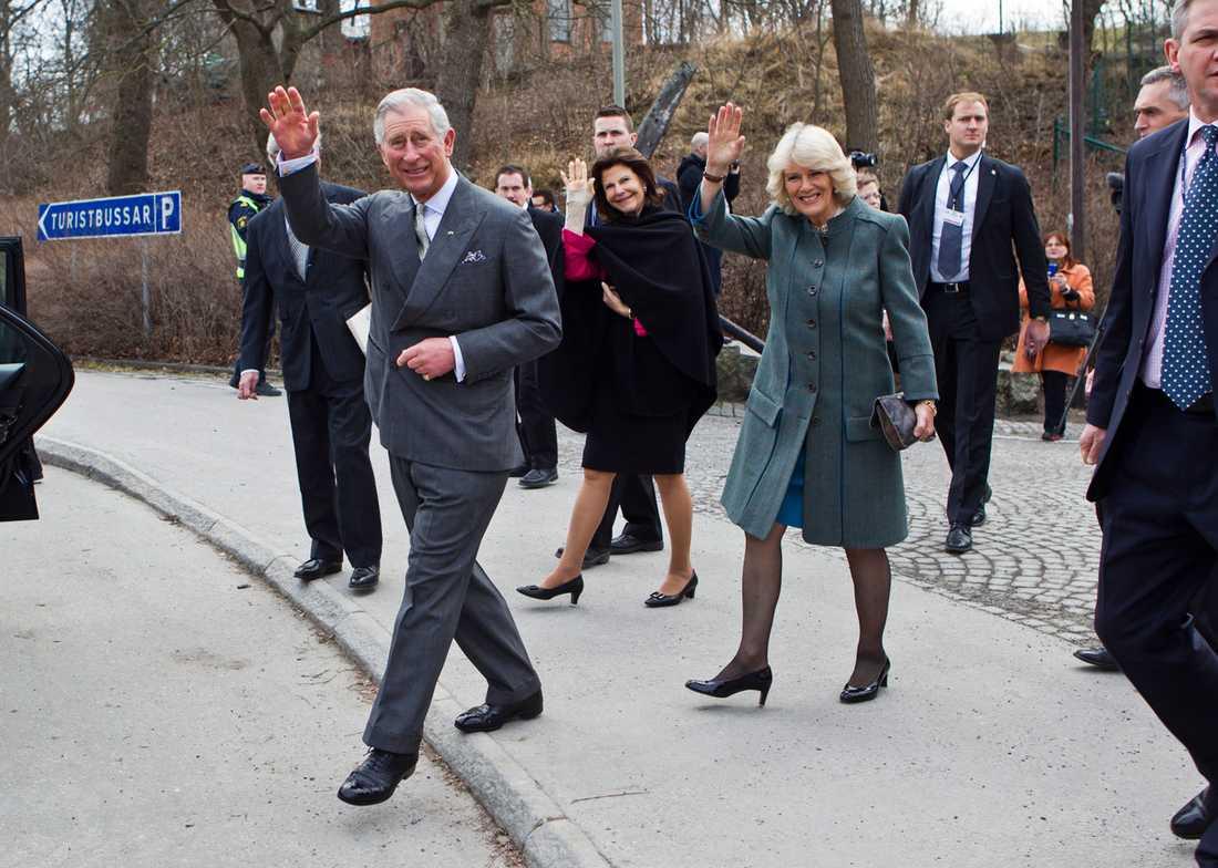 Prins Charles vinkar till nyfikna som samlats för att få se en glimt av kungligheterna.