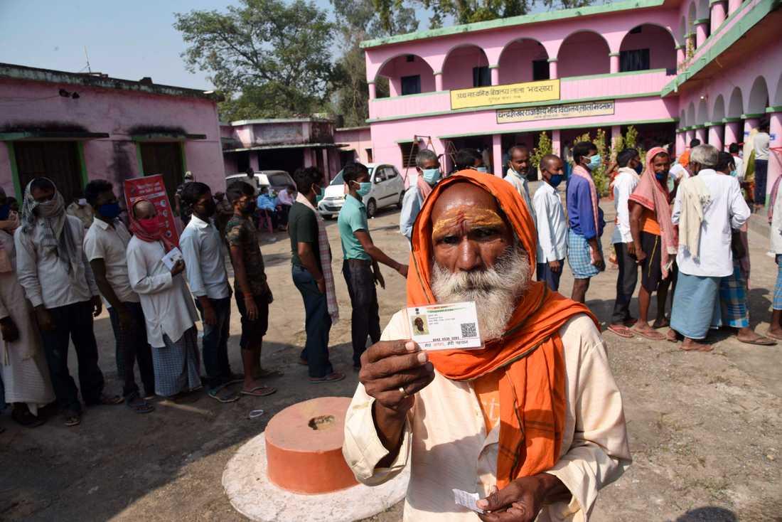 En väljare visar sitt id-kort utanför en vallokal i Palinganj i Bihar.