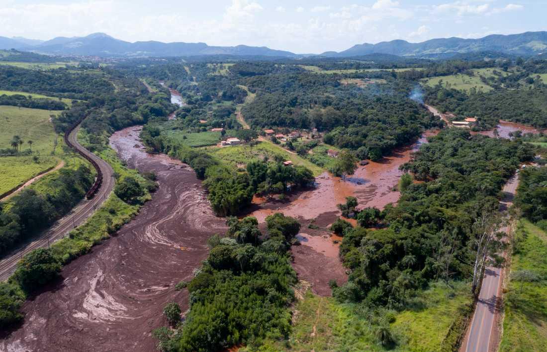 Leran som vällde ut från den kollapsade dammen har spridit sig över intilliggande åkrar och byggnader.