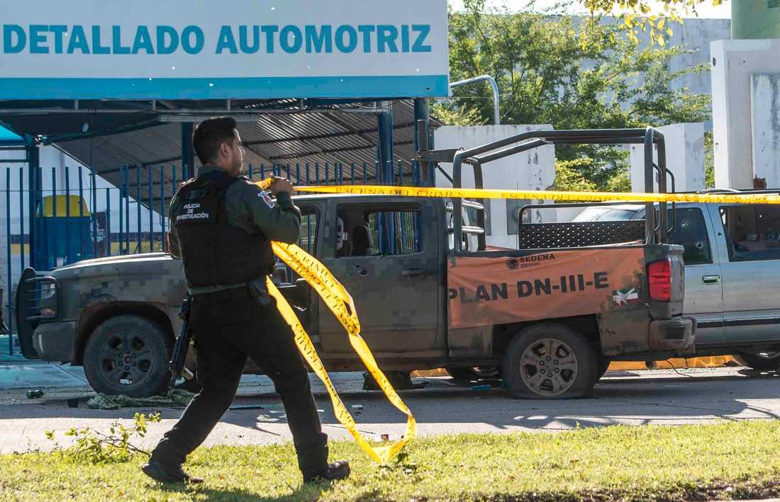 En mexikansk polis spärrar av platsen där ett av säkerhetsstyrkornas sönderskjutna fordon står.