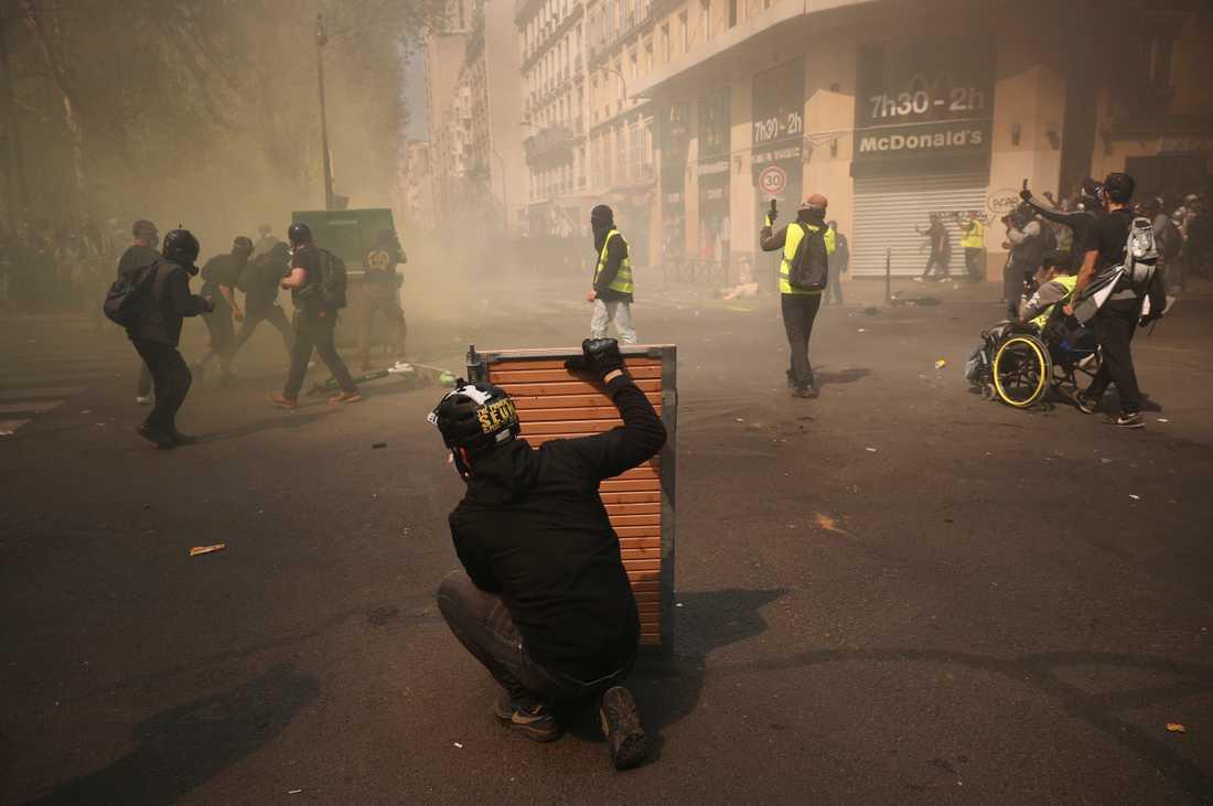 Demonstranter tar skydd bakom träpaneler vid sammandrabbningar i Paris.