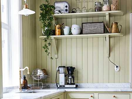Köket med lindblomsgrön pärlspont, vedspis och marmorbänk är Frida och Pontus extra nöjda med, eftersom det följer ursprunget i färg och stil. Bara ett av skåpen är i original och renoverat, övriga är nyproducerade men i samma stil.