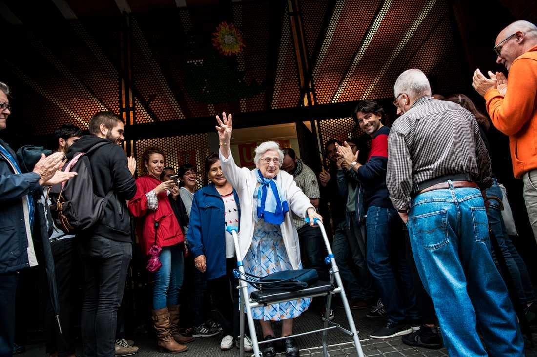 En äldre kvinna som lämnar röstningslokalen möts av jubel från människorna utanför.