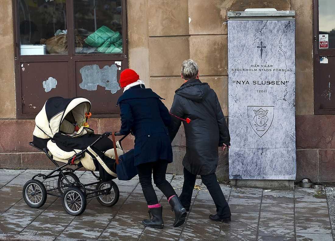 Någon har förvandlat ett elskåp på Skeppsbron i Stockholm till en gravsten över den nya Slussen.