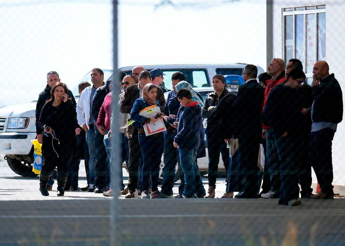 Passagerare från det kapade planet står och väntar på flygplatsen.