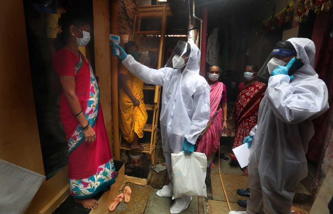 En vårdarbetare tar temperaturen på en kvinna i ett slumområde i indiska Bombay (Mumbai) i slutet av juni.