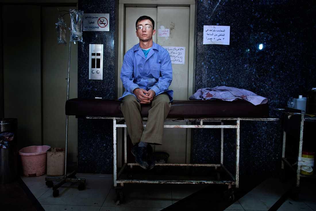 En man i sjukhuspersonalen tar en paus. Patienterna strömmar in till sjukhuset dag och natt, utan uppehåll.