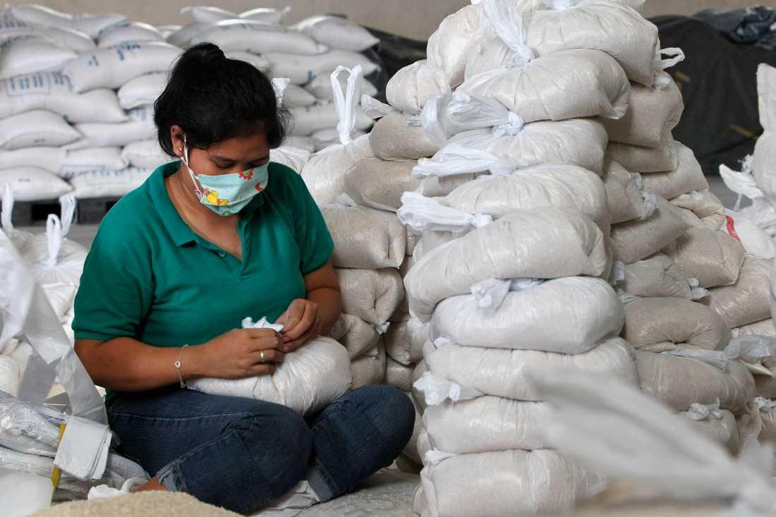En hjälparbetare i Manila packar säckar med ris som ska skickas till drabbade områden.
