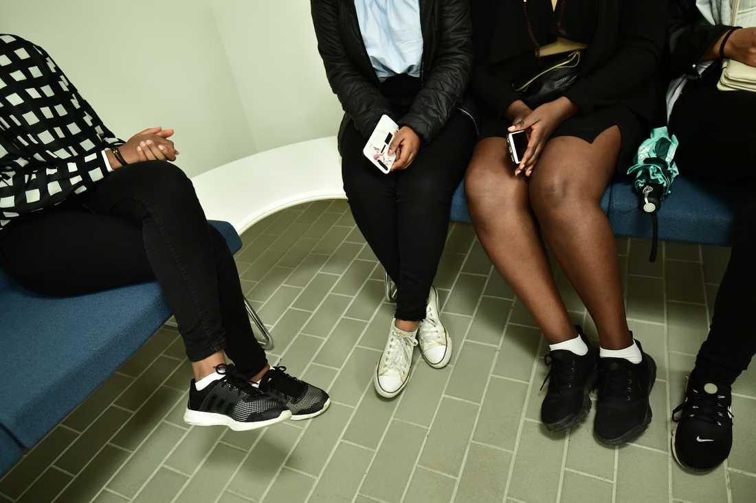 Fyra ungdomar sitter och väntar på att få komma in i åhörarsalen.