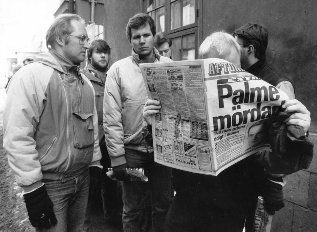 Människor läser i tidningen dagen efter mordet på statsminister Olof Palme den 28 februari 1986.