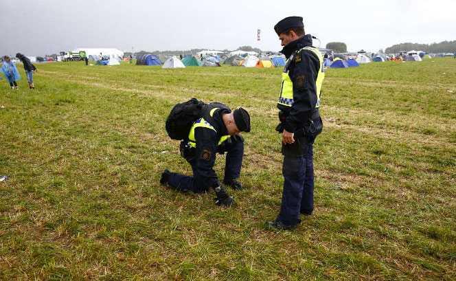 Poliser på plats undersöker marken efter blixtnedslaget.