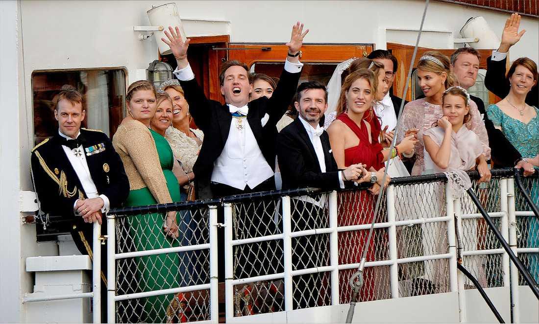 Chris O'Neill höjer armarna i skyn på partybåten på väg mot Drottningholm. Hela bröllopsföljet trängdes på fartygets brygga under den ljuvliga sommarkvällen på Mälaren. Hela viken var full av fritidsbåtar med folkmassor som vinkade och tjoade tillbaka.
