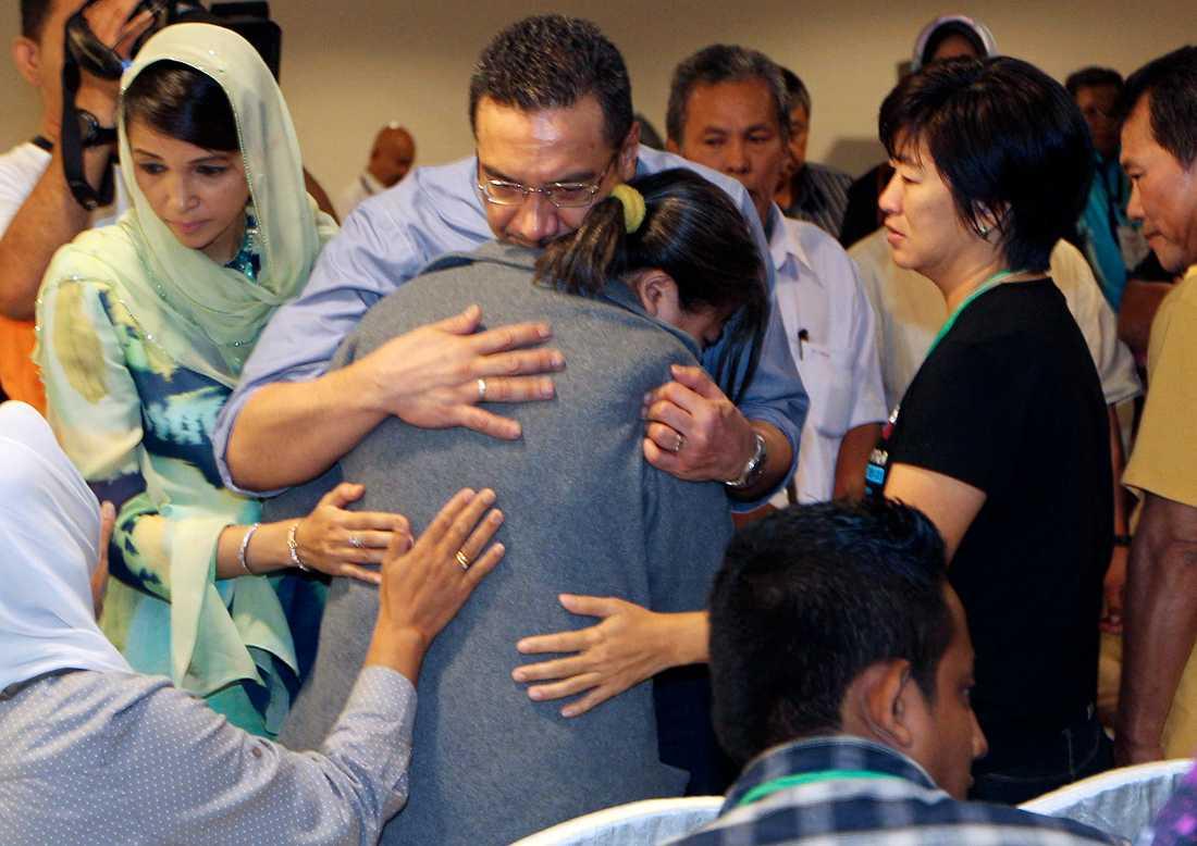 Malaysias transportminister tröstar en anhörig till en passagerare på MH370, efter att planet försvann.