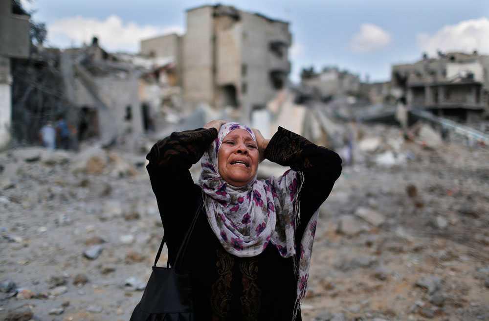 En kvinna i förtvivlan vid hennes förstörda hus i staden Beit Hanoun.