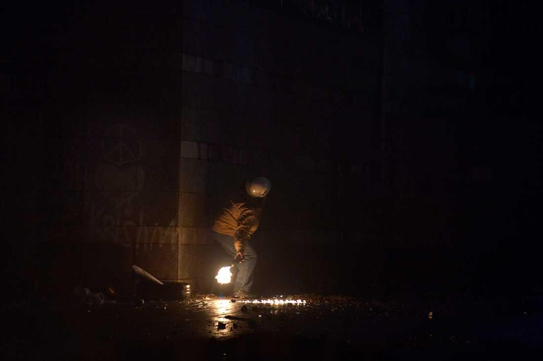En ensam man smyger sig upp emot muren där polisen har sitt fäste – med en molotov cocktail i handen.