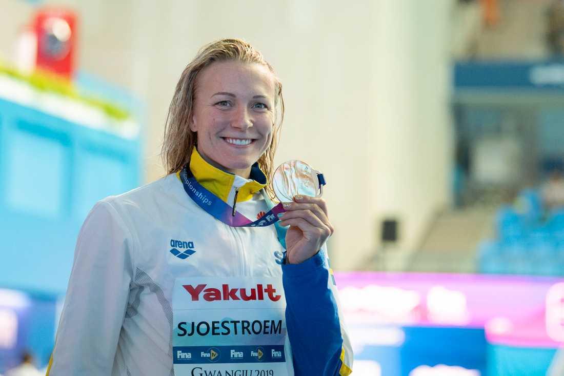 Sarah Sjöström visar upp VM-guldet på 50 meter fjäril i Gwangju. Nu väljer hon att avstå nästa mästerskap, kortbane-EM i december. Arkivbild.