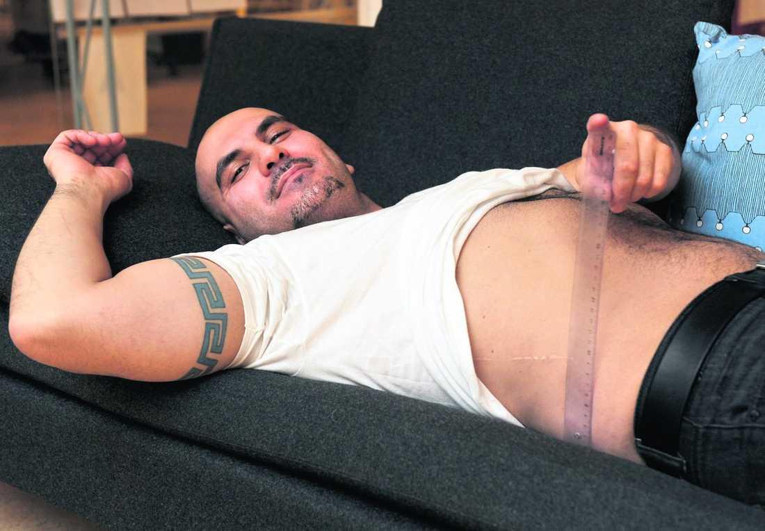 """Kocken Michel Bitar, 35, mäter hur hög hans mage är. Resultatet är godkänt. """"Nu kan jag dricka några öl till"""", konstaterar han."""