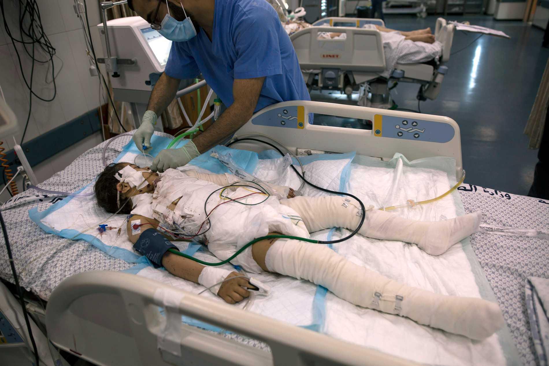 Palestisnk sjukvårdspersonal  tar han om en skadad flicka på Shifa hospital i Gaza City. Hon skadades i en attack mot familjens hus.