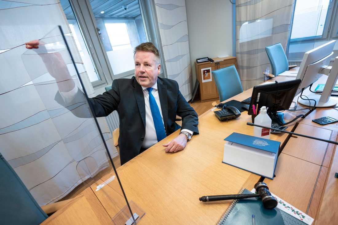 Lennart Strinäs, tillförordnad lagman i Malmö tingsrätt, visar de plexiglas som monterats mellan sittplatserna i en av rättssalarna i Malmö tingsrätt för att förhindra smittspridning på domarpodiet.