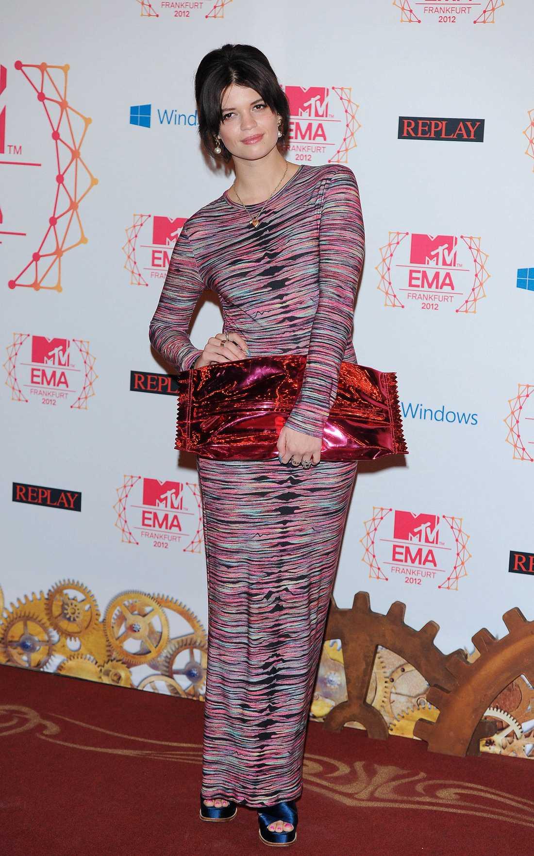 Pixie Geldof i långärmad klänning och en gigantisk karamell-väska i näven.