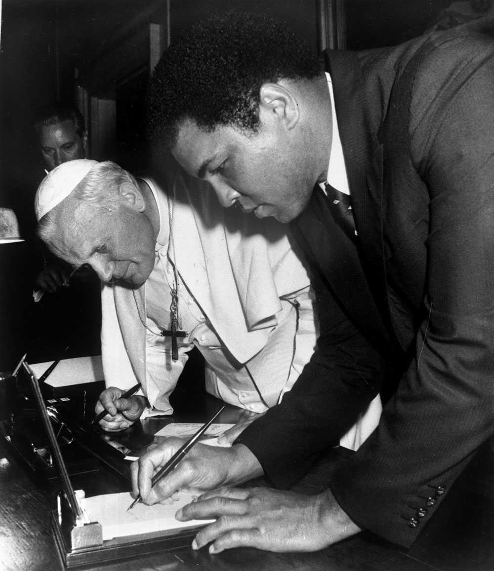 ALI OCH PÅVEN Påven John Paul II smygtittar på hur Muhammad Ali skriver sin autograf i Vatikanen 1982. Ali fick god träning på det under sin karriär.