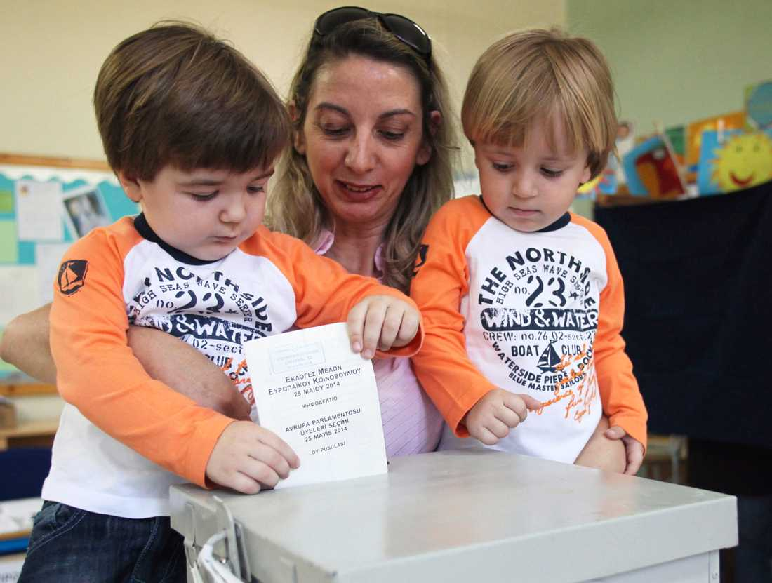 En mamma får hjälp att avge sin röst i en vallokal i Nicosia på Cypern.