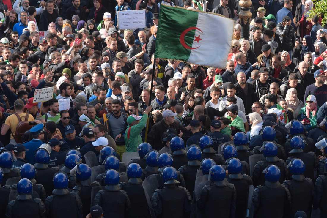 Säkerhetsstyrkor på rad framför demonstranter i Algeriets huvudstad Alger under protester på onsdagen.