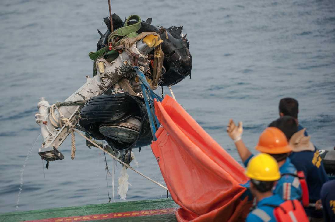 Vrakdelar från det kraschade planet plockas upp ur havet. Arkivbild.