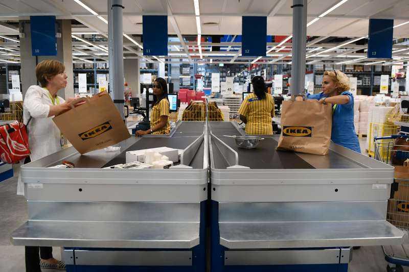 Sveriges generalkonsul i Mumbai, Ulrika Sundberg (till höger i bild), packar ner varor i en påse i den nya Ikea-butiken.