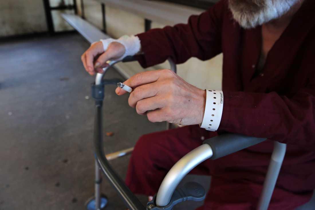 En äldre man vilar sig på rullatorn medan han tar en cigarett på ett sjukhus i Boston i USA. Sjukhuset har nyligen beslutat att förbjuda rökning på sjukhusområdet. De senaste 20 åren har många länder i världen infört starkare kontroll av tobak, delvis på grund av WHO:s ramkonvention för tobakskontroll.