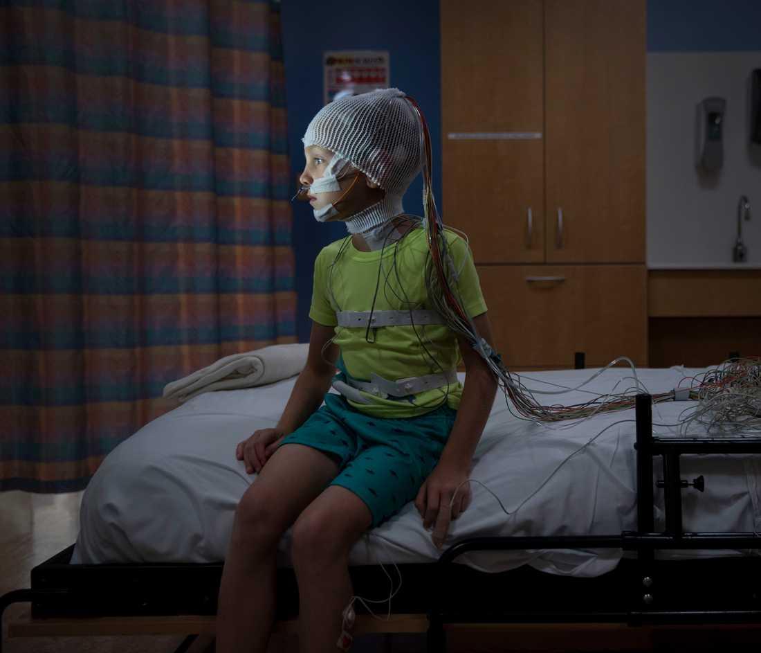 """Bra sömn är livsviktigt för barns hälsa och utveckling. Åttaårige Michael Bosak är täckt av kablar och elektroder när han väntar på """"läggdags"""". Han deltar i en sömnstudie i Childrens National Health systems regi I USAs huvudstad Washington. Han testas för sömnaden, ett tillstånd då han får andningsuppehåll vid upprepade tillfällen under natten."""