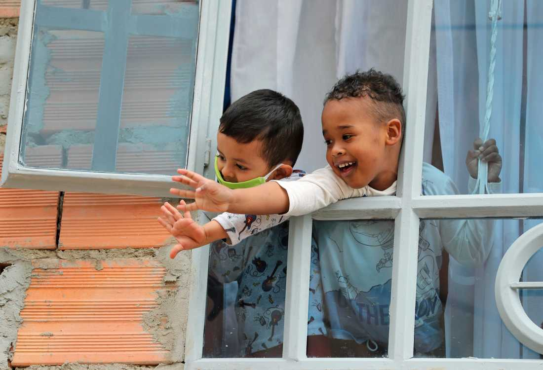 Barn vinkar till soldater som hjälper till att dela ut mat till behövande i Bogota i Colombia. Staden delar ut mat till människor som inte längre kan gå till jobbet på grund av pandemins restriktioner.