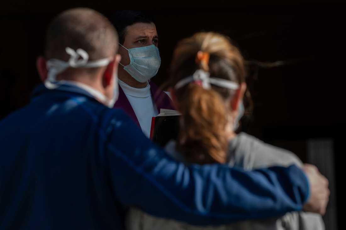 En präst med ansiktsmask håller en begravning i Madrid.