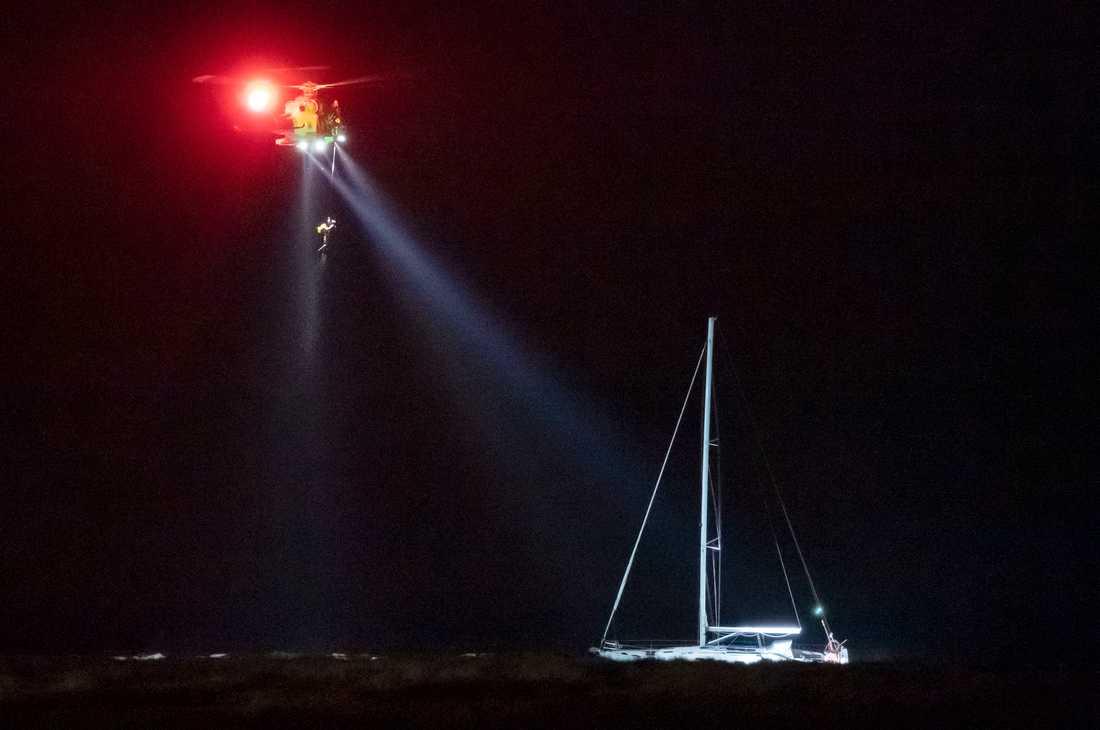 Sjöräddningens helikopter vinschar upp en person vid den grundstötta segelbåten vid Falsterbo fyr på tisdagskvällen. Arkivbild.