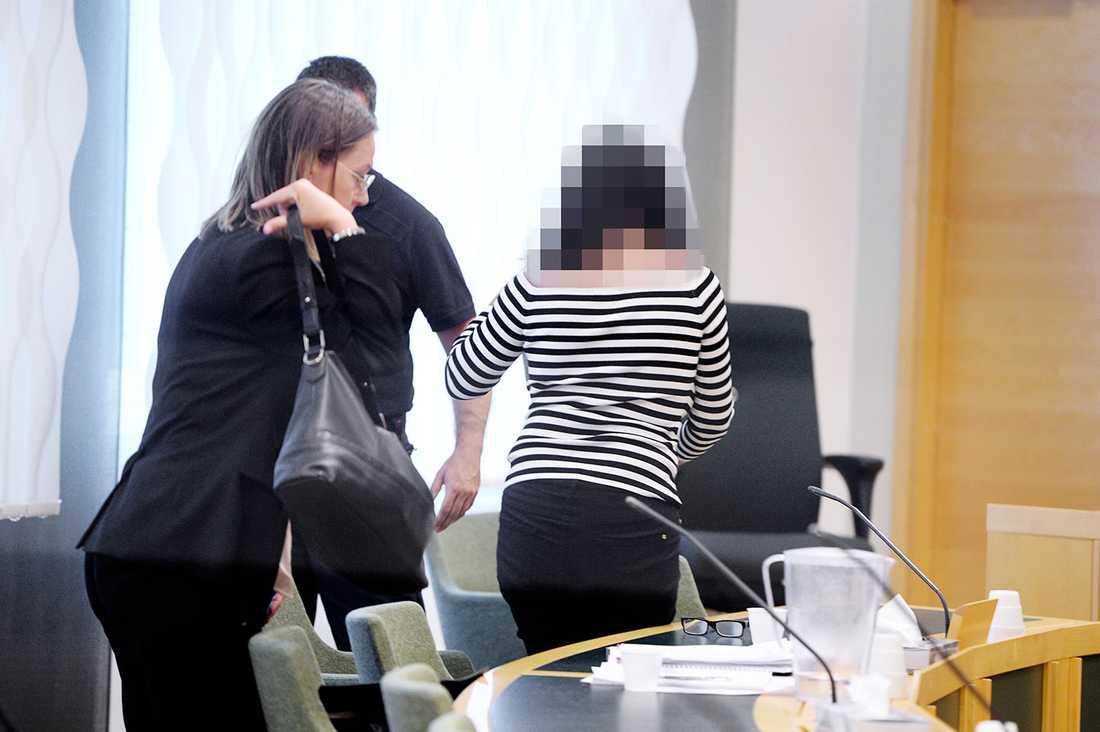 Den 41-åriga dottern lämnar rättssalen efter att ha häktats för mord och mordförsök på föräldrarna.