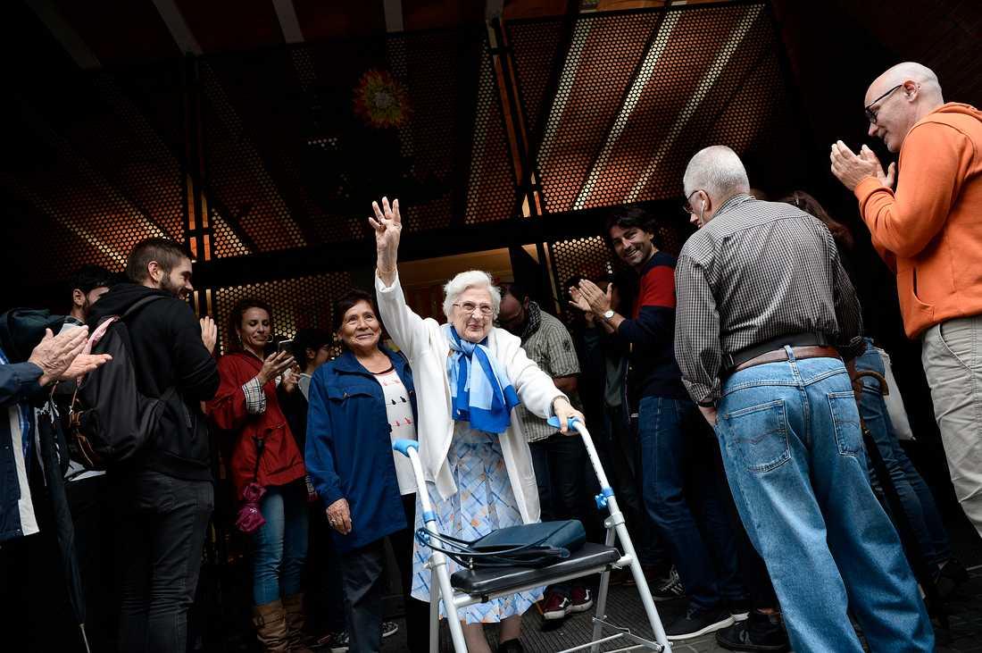 En äldre kvinna som röstat möts av applåder när hon kommer ut från vallokalen.