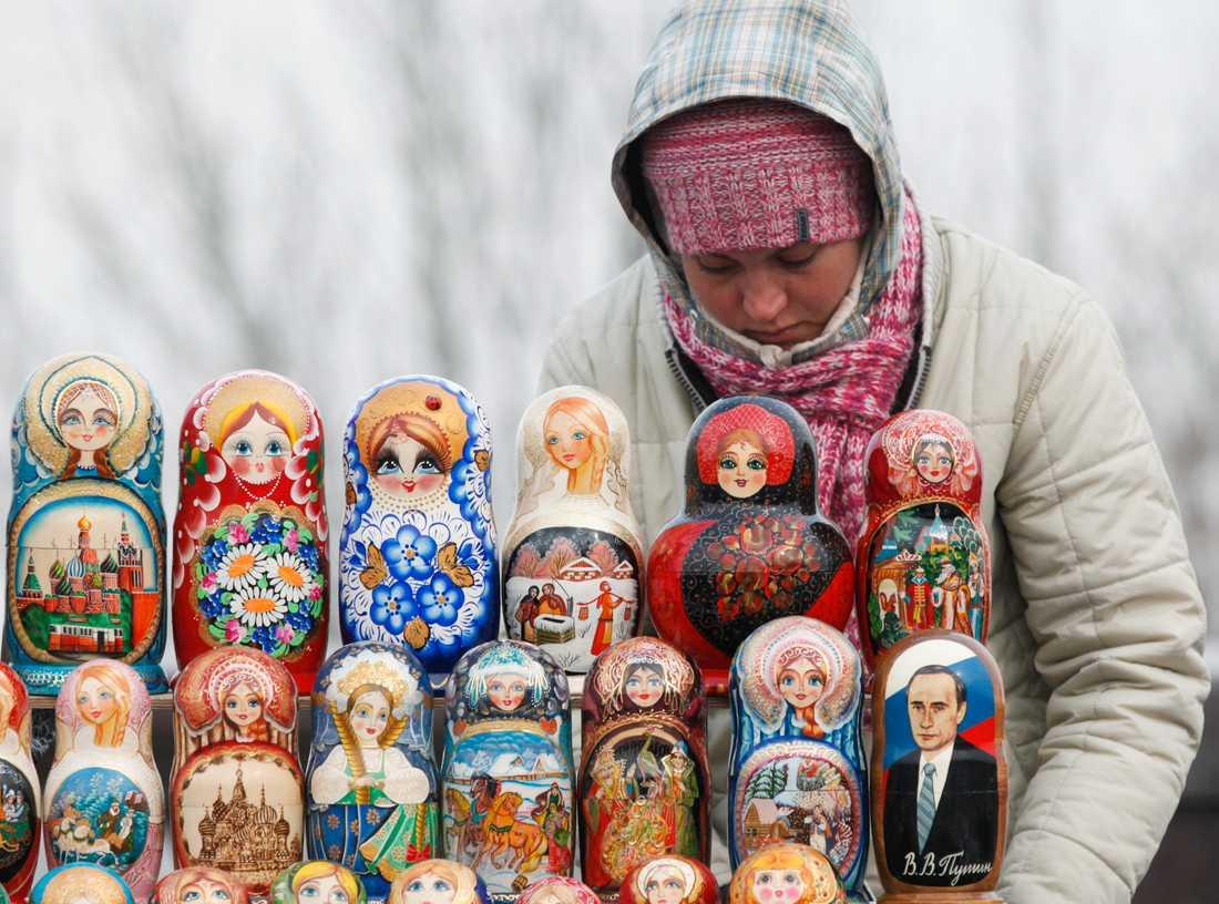 Rysk souvernir Kvinnan säljer traditionella babushka dockor i Moskva. Ett med Putin som motiv.