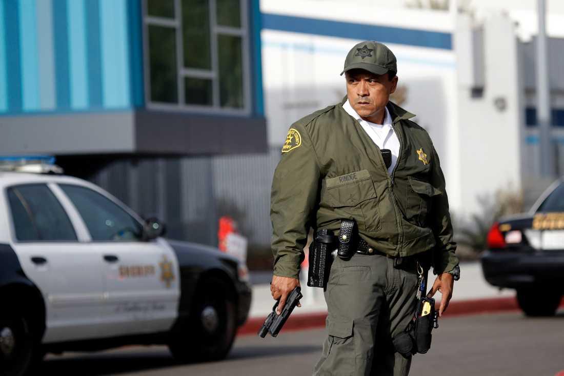 En polis från Los Angeles polisstation står med draget vapen utanför Saugus High School.